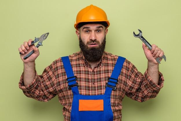 緑の背景の上に立って混乱し、驚いたカメラを見てレンチとペンチを保持している建設制服と安全ヘルメットのひげを生やしたビルダーの男