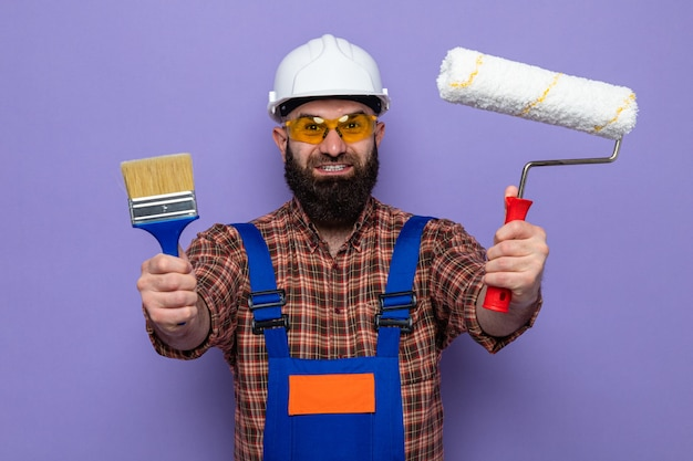Бородатый мужчина-строитель в строительной форме и защитном шлеме в желтых защитных очках, держащий валик и кисть, смотрящий в камеру счастливым и возбужденным, улыбаясь, стоя на фиолетовом фоне