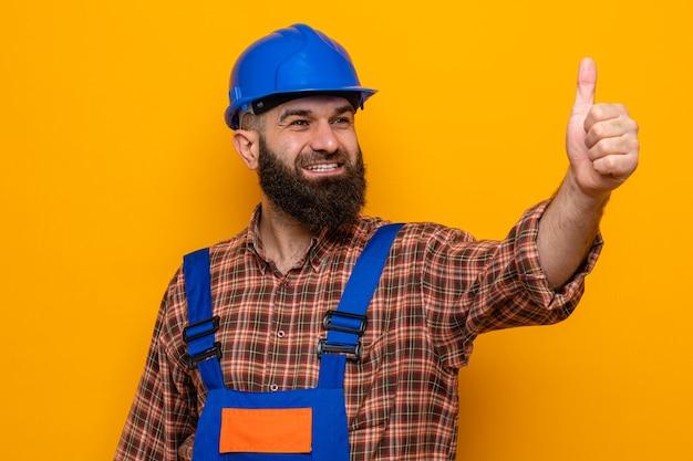 Бородатый мужчина-строитель в строительной форме и защитном шлеме смотрит в сторону, весело улыбаясь, радостно и позитивно показывает палец вверх