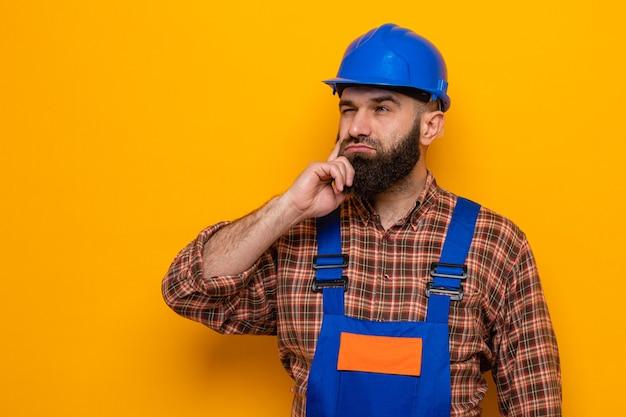 オレンジ色の背景の上に立って物思いにふける表現思考を脇に見ている建設制服と安全ヘルメットのひげを生やしたビルダー男