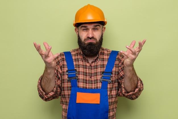 건설 유니폼과 안전 헬멧을 쓴 수염 난 건축업자가 녹색 배경 위에 서 있는 혼란스러운 어깨를 으쓱하고 있는 카메라를 바라보고 있다