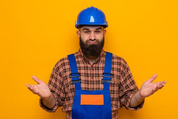 オレンジ色の背景の上に立っている側に腕を広げて混乱したカメラを見て建設制服と安全ヘルメットのひげを生やしたビルダーの男