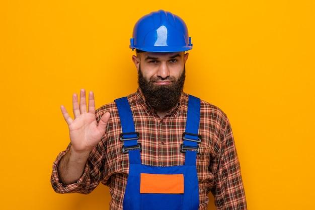 Бородатый мужчина-строитель в строительной форме и защитном шлеме, недовольно глядя в камеру, показывает жест стоп с рукой, стоящей на оранжевом фоне