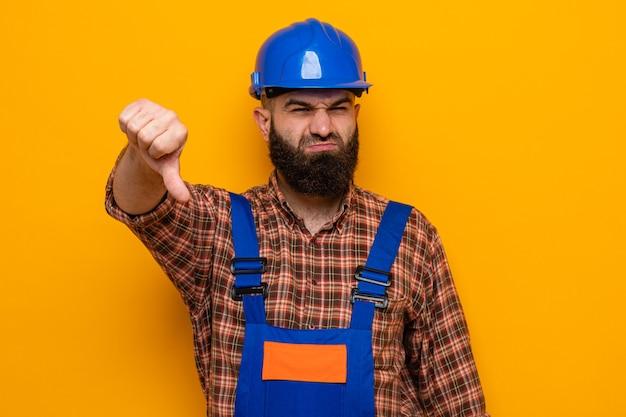 オレンジ色の背景の上に立って親指を下に見せて不機嫌なカメラを見て建設制服と安全ヘルメットのひげを生やしたビルダー男