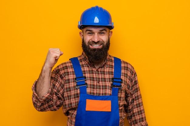 オレンジ色の背景の上に元気に立って笑顔の幸せで興奮した握りこぶしを握りしめてカメラを見て建設制服と安全ヘルメットのひげを生やしたビルダーの男