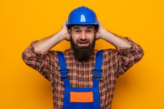 Бородатый мужчина-строитель в строительной форме и защитном шлеме смотрит в камеру счастливым и взволнованным, держась за руки на голове, стоя на оранжевом фоне