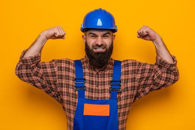 건설 유니폼과 안전 헬멧을 쓴 수염 난 건축업자가 주황색 배경 위에 서 있는 승자처럼 행복하고 흥분된 주먹을 들고 카메라를 바라보고 있습니다. 프리미엄 사진