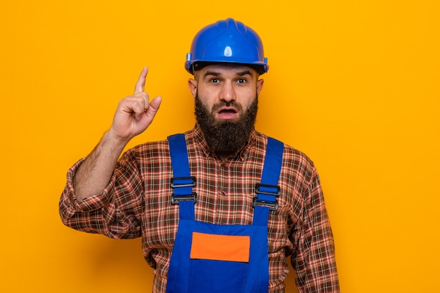 건설 유니폼 및 안전 헬멧 수염 작성기 남자 카메라 행복하고 놀란 보여주는 검지 손가락 오렌지 배경 위에 서있는 새로운 아이디어를 갖는