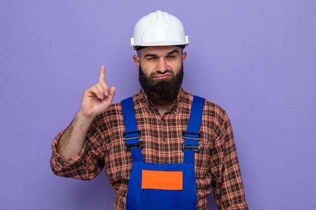 보라색 배경 위에 서 있는 검지 손가락을 보여주는 자신감 있는 표정으로 카메라를 바라보는 건설 유니폼과 안전 헬멧을 쓴 수염 난 건축업자