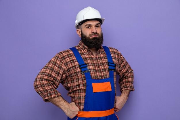 보라색 배경 위에 손으로 엉덩이를 잡고 자신감 있는 표정으로 카메라를 바라보는 건설 유니폼과 안전 헬멧을 쓴 수염 난 건축업자
