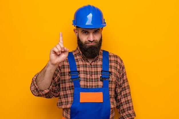 オレンジ色の背景の上に立っている人差し指の警告ジェスチャーを示す深刻な顔でカメラを見て建設制服と安全ヘルメットのひげを生やしたビルダーの男