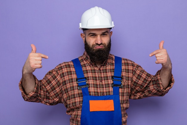 Бородатый строитель в строительной форме и защитном шлеме выглядит уверенно улыбаясь, указывая на себя, стоящего на фиолетовом фоне