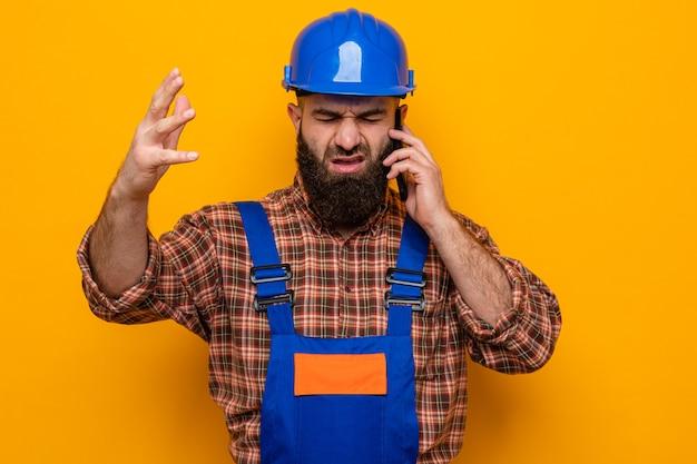 건설 유니폼과 안전 헬멧을 쓴 수염 난 건축업자 남자가 휴대전화로 통화하는 동안 혼란스럽고 좌절한 표정으로 팔을 들어 올렸다