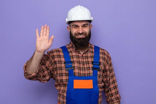건설 유니폼과 안전 헬멧을 쓴 수염 난 건축업자 남자는 손바닥으로 다섯 번째를 즐겁게 보여주며 웃고 있습니다