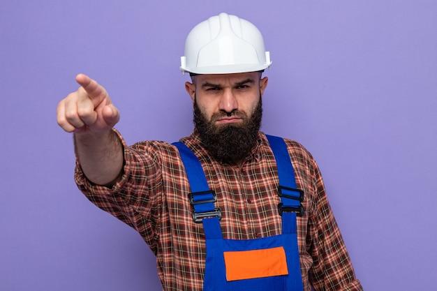 건설 유니폼과 안전 헬멧을 쓴 수염 난 건축업자가 앞을 가리키는 검지 손가락으로 찡그린 얼굴을 하고 있다