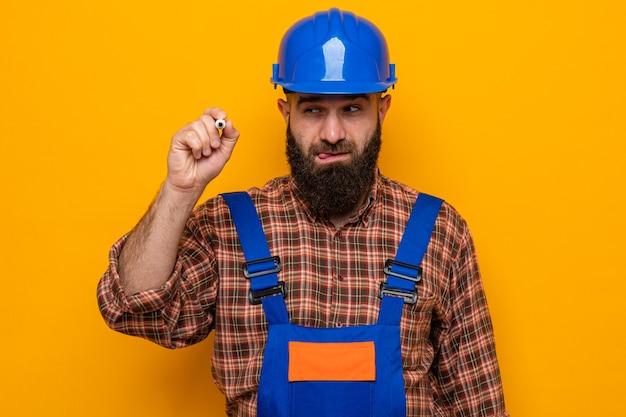 オレンジ色の背景の上に立っている空気中のペンで真剣な顔の書き込みでずるい笑顔で見て建設制服と安全ヘルメットのひげを生やしたビルダーの男
