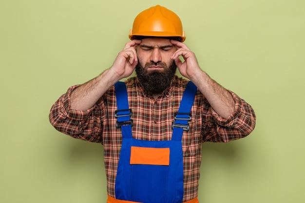 건설복을 입은 수염난 건축업자, 관자놀이를 만지는 안전모