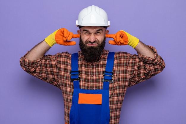 Бородатый мужчина-строитель в строительной форме и защитном шлеме в резиновых перчатках закрывает уши пальцами с раздраженным выражением лица, стоя на фиолетовом фоне