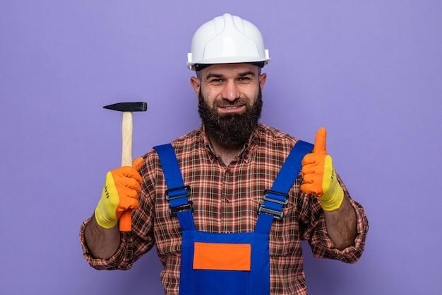 Бородатый мужчина-строитель в строительной форме и защитном шлеме в резиновых перчатках держит молоток, уверенно улыбается и показывает палец вверх
