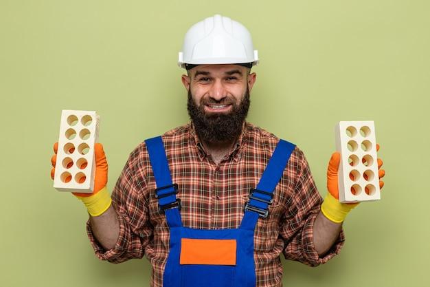 緑の背景の上に元気に幸せで前向きに立って笑顔のカメラを見てレンガを保持しているゴム手袋を身に着けている建設制服と安全ヘルメットのひげを生やしたビルダーの男