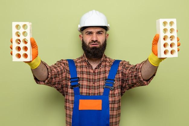 녹색 배경 위에 서 심각한 얼굴로 카메라를 찾고 벽돌을 들고 고무 장갑을 끼고 건설 유니폼과 안전 헬멧에 수염 작성기 남자