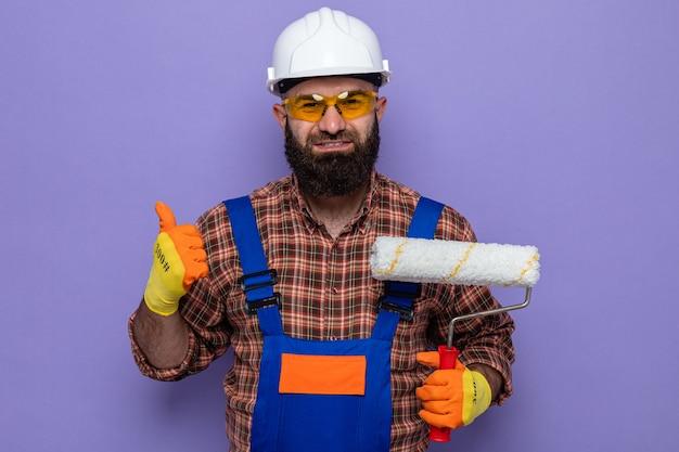 Бородатый мужчина-строитель в строительной форме и защитном шлеме в резиновых перчатках держит валик с краской, глядя в камеру, улыбаясь, показывая пальцы вверх, стоя на фиолетовом фоне