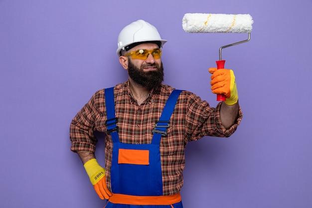 보라색 배경 위에 서 있는 행복한 얼굴에 미소를 지으며 페인트 롤러를 들고 고무 장갑을 끼고 고무 장갑을 끼고 건설 유니폼을 입은 수염 난 건축업자
