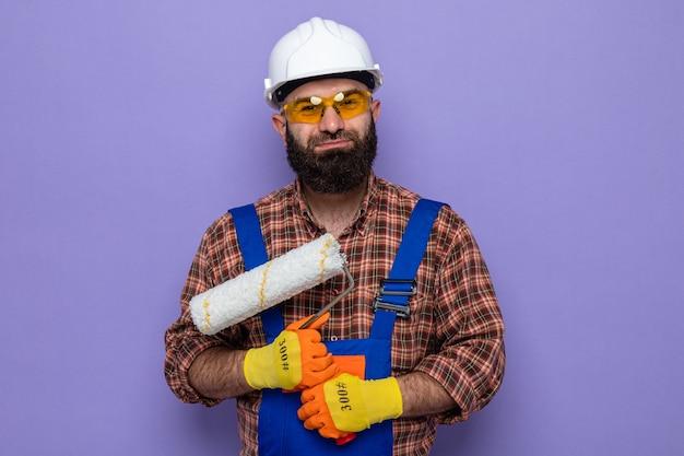 Бородатый строитель в строительной форме и защитном шлеме в резиновых перчатках держит валик с краской, выглядит счастливым и позитивно улыбается