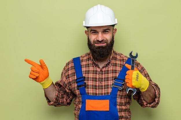 Бородатый строитель в строительной форме и защитном шлеме в резиновых перчатках держит гаечный ключ и улыбается, указывая указательным пальцем в сторону