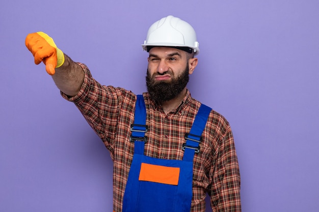 Бородатый строитель в строительной форме и защитном шлеме в резиновых перчатках недовольно смотрит в сторону и показывает палец вниз