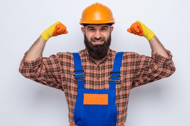 흰색 배경 위에 서 있는 승자처럼 자신감 있게 주먹을 들고 웃고 있는 카메라를 바라보며 고무장갑을 끼고 건설 유니폼을 입은 수염 난 건축업자