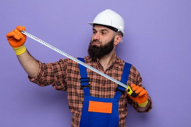 측정 테이프를 사용하여 자신감 있게 작업하는 고무 장갑을 끼고 건설 유니폼과 안전 헬멧을 쓴 수염 난 건축업자