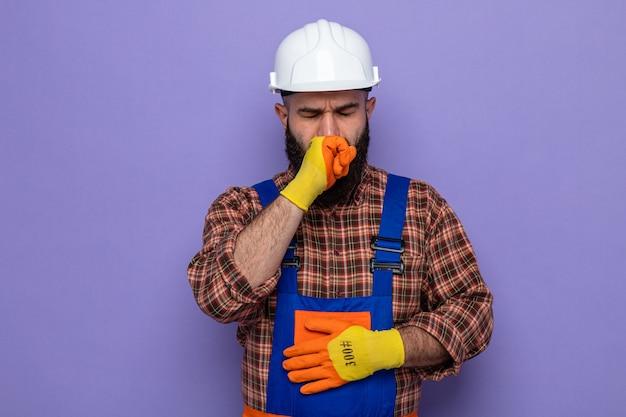 보라색 배경 위에 서 있는 주먹에 몸이 좋지 않은 것처럼 보이는 고무 장갑을 끼고 건설 유니폼과 안전 헬멧을 쓴 수염 난 건축업자