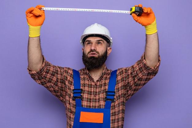 측정 테이프를 사용하여 작업하는 자신감 있는 표정으로 올려다보는 고무 장갑을 끼고 건설 유니폼과 안전 헬멧을 쓴 수염 난 건축업자