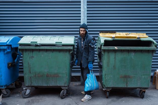 街の通りのゴミ箱で食べ物を探しているひげを生やしたお尻。