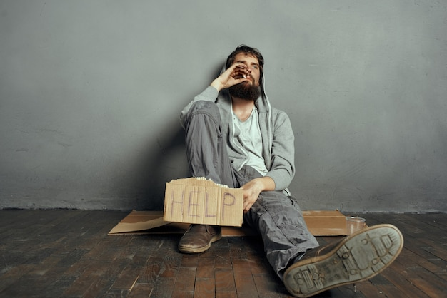 Бородатый бомж сидит на полу с табличкой помогите образу жизни депрессии. фото высокого качества
