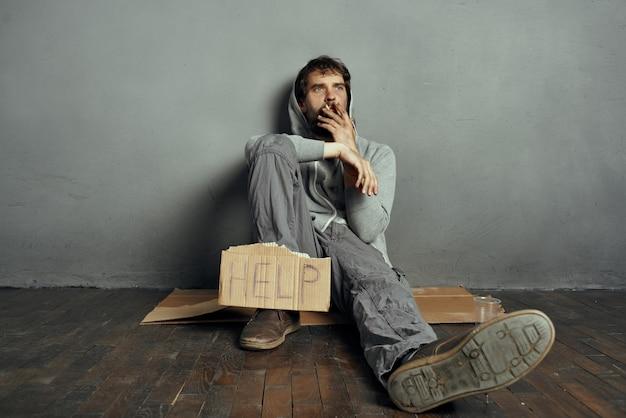 수염 난 부랑자는 우울증 생활 방식에 도움이 되는 표지판을 들고 바닥에 앉아 있습니다.