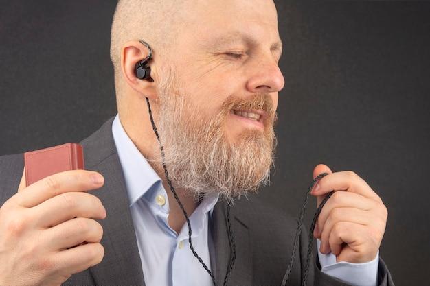 ひげを生やしたビジネスマンは、小さなヘッドホンでオーディオプレーヤーからお気に入りの音楽を聴くのを楽しんでいます。