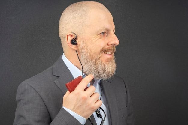 ひげを生やしたビジネスマンは彼の好きな音楽を聴くのが好きです