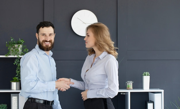 Bearded businessman and businesswoman shaking hands in office