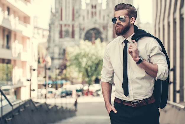 Bearded businessman in classic suit and sun glasses.