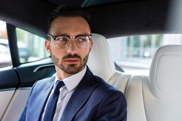 あごひげを生やした実業家。オフィスに行く途中で車の後部座席に座っている暗い目のひげを生やしたビジネスマン