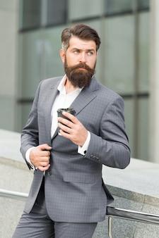 Бородатый бизнесмен пьет кофе на вынос. формальный мужчина в костюме офиса, пить кофе из бумажного стаканчика. доброе утро кофе. забери пить. уверенному бизнесмену нужно вдохновение.