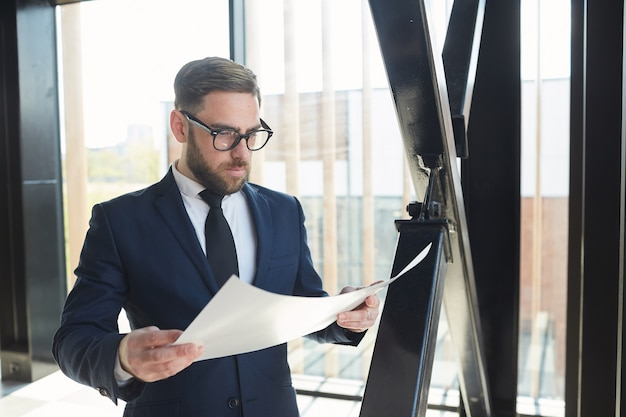 Bearded businessman in eyeglasses and in blue suit examining the business contract while standing at office