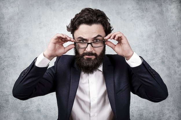 Bearded businessman holds the glasses with his hands and frowns