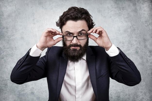 Бородатый бизнесмен держит очки руками и хмурится