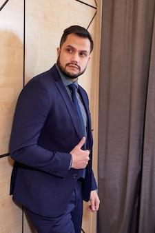 会議室で隔離されたカメラでポーズをとって、横を見て、自信を持って真剣に立っているエレガントな青いスーツのひげを生やしたビジネスマン。ビジネスマンの概念