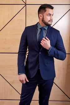 エレガントな青いスーツのひげを生やしたビジネスマンは、会議室で隔離され、自信を持って真剣に横を見て立っています。ビジネスマンの概念