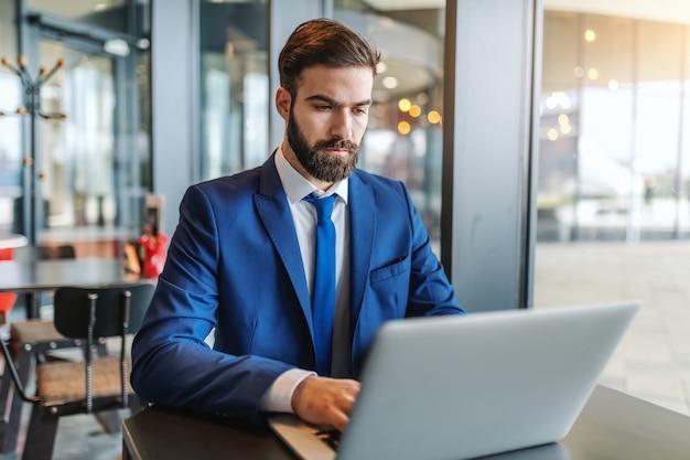 ウィンドウの横にあるカフェテリアに座っている間にラップトップを使用して深刻な表情を持つフォーマルな服装のひげを生やした実業家。