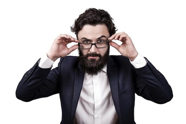 Бородатый бизнесмен изолирован на белом фоне, приподнял бровь и смотрит на зрителя